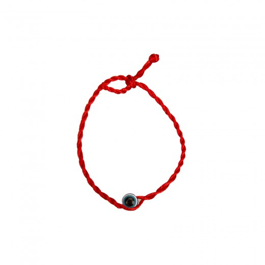 The bracelet on the arm, red thread with a blue bead