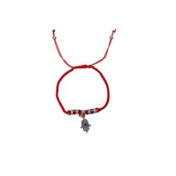 Bracelet on the hand of the red thread with hanging Hamsa