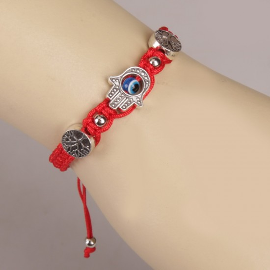 Bracelet on hand on a red string, on both sides is an additional element of the tree of life