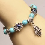 Bracelet on hand, turquoise base, pendant anchovy, silver color